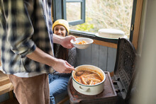 Happy Young Couple Making Stew In Tiny Cabin Rental