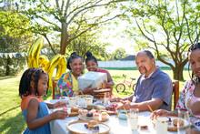 Multigenerational Family Celebrating Birthday In Summer Backyard