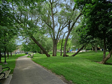 Local Neighborhood Park In An Urban Area With Grass, Shade Trees, And Benches Around A Path
