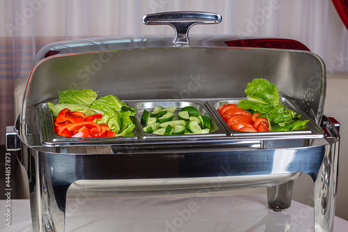 Fototapeta A chafing-dish with sliced vegetables and salad.