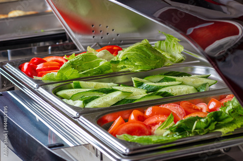 Fotografie, Obraz Lettuce, peppers, sliced cucumbers and tomatoes on trays.