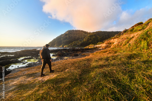 Fotografia Man with backpack walking on the oceanside trail at sunset time for a camping