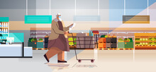 Senior Woman With Full Of Products Trolley Cart Checking Shopping List In Supermarket