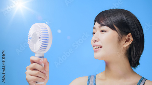 Photo ハンディファンとネックファンを使う女性 ポータブル扇風機