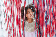 Happy Girl Looking At Camera Standing Near Foil Curtain