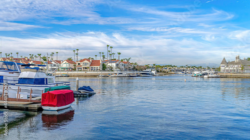 Fotografia Pano Houses and docks along sea viewed from the sandy shore in Huntington Beach