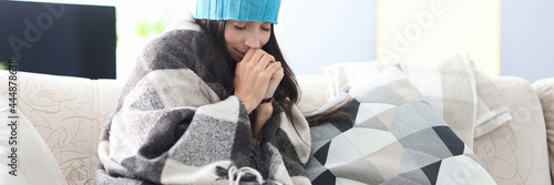 Fotografía Frozen woman in hat and blanket sits on couch