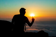 Silhouette Of A Man Touching The Sun With A Finger, On Top Of A Mountain. Sunset And Cloud Sky Background.