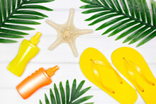 Summer Sea Beach Vacation Creative Concept. Sunscreen Spray, Flip Flop Sandals, Starfish With Tropical Palm Leaves On White Wooden Boards. Top View, Flat Lay