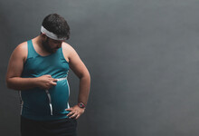 Fat Young Man Measuring His Belly With A Tape Measure.
