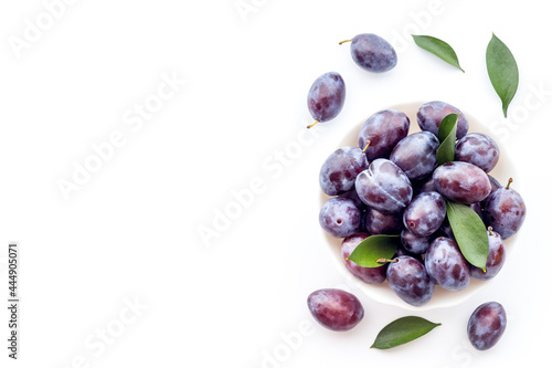 Fotografie, Obraz Purple plums with leaves top view. Food fruits background