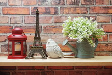 Home Decoration With Red Lantern, Eiffel Tower, Bird Statue And Artificial Plant On Wooden Shelve