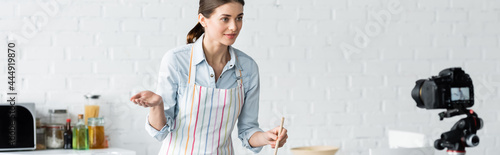 Foto young culinary blogger pointing with hand near digital camera in kitchen, banner