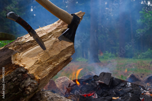Obraz na plátně Camp fire in a forest with chopper in wood
