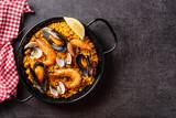 Fototapeta Kawa jest smaczna - Traditional spanish seafood paella on black background. Top view. Copy space
