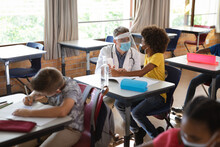 Caucasian Male Doctor Wearing Face Shield Measuring Temperature Of African American Boy At School