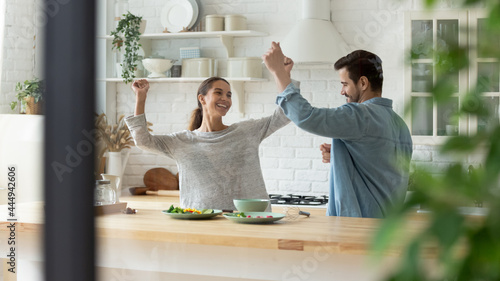 Foto Carefree active millennial couple dancing together in cozy modern kitchen, liste