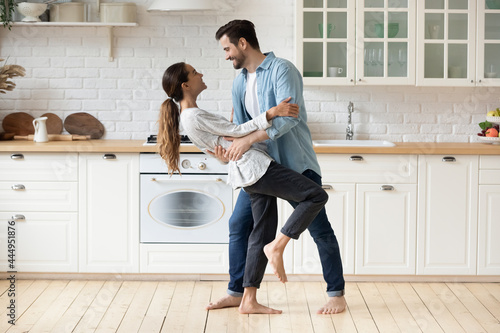 Foto Young beautiful mixed race couple home owners family celebrate relocation day housewarming dancing in modern cozy kitchen standing barefoot on warm floor feel happy