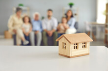 Closeup Of Small Little Toy House On Table Against Blurred Background Of Living-room With Whole Big Family Of Mom, Dad, Grandma, Grandpa And Kids Sitting Together. Real Estate, Buying New Home Concept