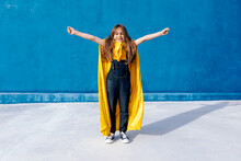 Cheerful Teenager In Cape Of Superhero On Blue Background
