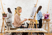 Woman Painting On Canvas In Art Workshop