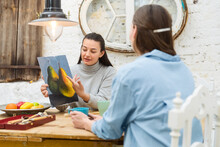 Women Drinking Tea In Art Studio And Discussing Painting