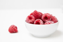 Frozen Raspberries In A White Bowl On A White Background