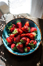 Strawberries In A Blue Bowl In A Rustic Kitchen