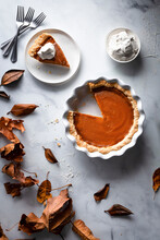 Pumpkin Pie On A Marble Surface With Whipped Cream