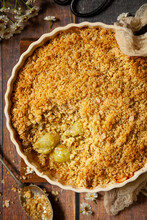 A Gooseberry Crumble In A Baking Dish With A Portion Removed To Reveal The Fruit Layer Under The Crisp Topping