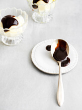 Hot Fudge Sundaes In Background With Messy Hot Fudge Spoon In The Forground. Bright And Sunny On A Metal Surface.