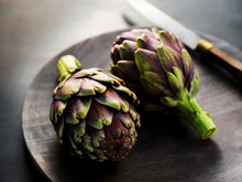 2 Fresh Artichokes On A Wood Tray And Dark Surface With Dramatic Lighting.