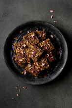 Pistachio Brownies Garnished With Dried Rose Petals On A Dark Ceramic Plate