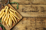 Fresh baby corn cobs and spices on wooden table, flat lay. Space for text