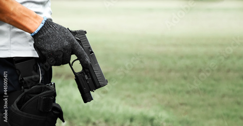 Automatic 9mm pistol which has flashlight under the muzzle holding in hand and ready to shoot, natural blurred background Fotobehang