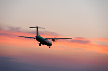 The Plane Landing On The Sunset Background