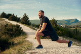 Male athlete warming up before start running in mountains