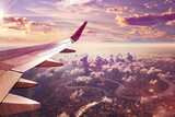 Fototapeta Zwierzęta - Flight and journey to destination. Concept of airplane travel. Flying above the city. Scenery sunset landscape.Sunrise and clouds.