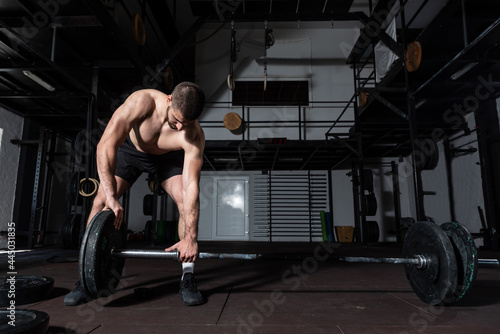 Fototapeta Young active sweaty strong muscular fit man with big muscles putting heavy iron
