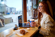 Leinwandbild Motiv Young pretty hipster woman with red hair sit using modern laptop, vintage camera in stylish cafeteria. Adorable caucasian female with coffee on freelance.copy space