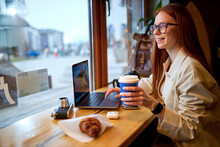 Young Pretty Hipster Woman With Red Hair Sit Using Modern Laptop, Vintage Camera In Stylish Cafeteria. Adorable Caucasian Female With Coffee On Freelance.copy Space
