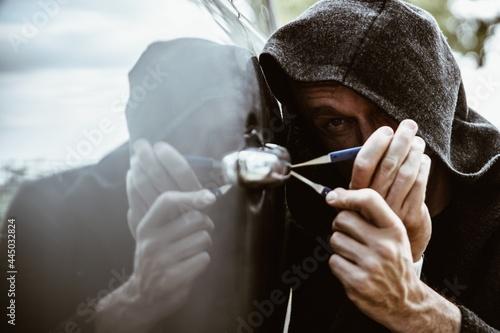 Fototapeta A car thief opening a car door with a lockpicer. Burglar.
