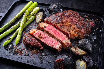 Modern style barbecue dry aged wagyu rib-eye beef steaks with green asparagus and charred onions served as close-up on a black cast iron design tray