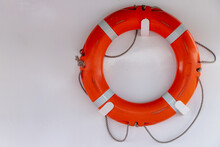 Safety Concept, Selective Focus Of Lifebuoy Hanging On White Wall, Old Used Red Ring Buoy With The Rope On The Boat, Water Wheely Is A Life Saving Buoy Designed To Be Thrown To A Person In The Water.