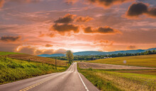 Long Straight Empty Road Through The Green Grassy Field Under Bright Cloudy Sunset Sky
