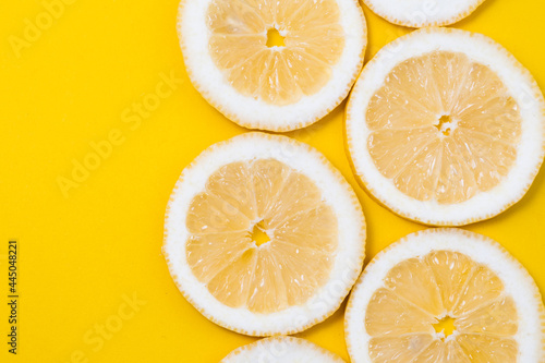 Fotografiet slices of fresh yellow lemon on yellow background