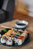 Vertical shot of a plate of assorted sushi on a wooden table next to soy sauce and chopsticks