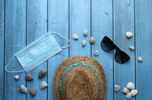 A Straw Hat, Pebbles And Shells, Sunglasses And A Protective Mask On A Blue Wooden Background. The Concept Of Recreation And Entertainment In The Context Of The Coronavirus Pandemic.