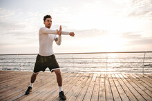 Attractive Charming Dark-skinned Sportsman In Black Shorts And White Long-sleeved T-shirt Does Ark Exercises, Stretches And Works Out Near Sea.