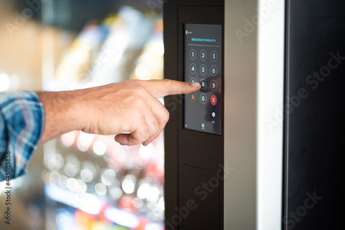Fototapeta Close up of man hand typing number code on touch screen display - concept of sec